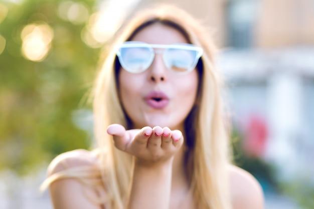 Sprint positief portret van gelukkige vrolijke jonge vrouw die luchtkus naar u verzendt, een duidelijke bril draagt, focus aan de kant, pastelkleurige kleuren. Gratis Foto