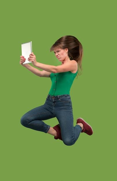 Sprong van jonge vrouw over groene studioachtergrond die laptop of tabletgadget met behulp van tijdens het springen. Gratis Foto