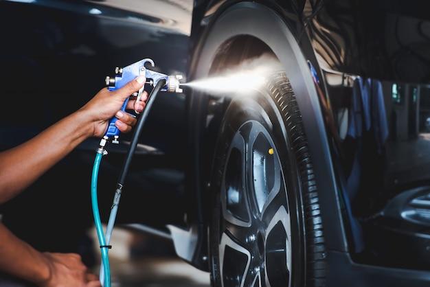 Spuit de banden na het wassen van de auto om de banden te laten schitteren en zwart te maken. - zet de band in de was Premium Foto