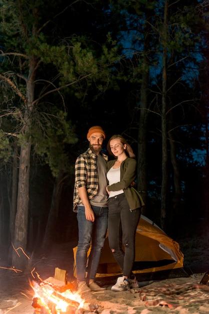 Staand paar dat het kampvuur bekijkt Gratis Foto