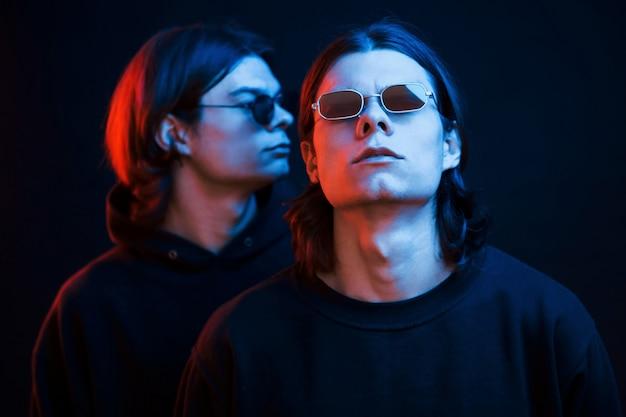 Staande in de zwarte kleren. portret van tweelingbroers. studio opname in donkere studio met neonlicht Premium Foto