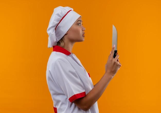 Staande in profiel bekijken jonge kok vrouwelijke chef-kok uniform houden mes op geïsoleerde oranje achtergrond met kopie ruimte dragen Gratis Foto