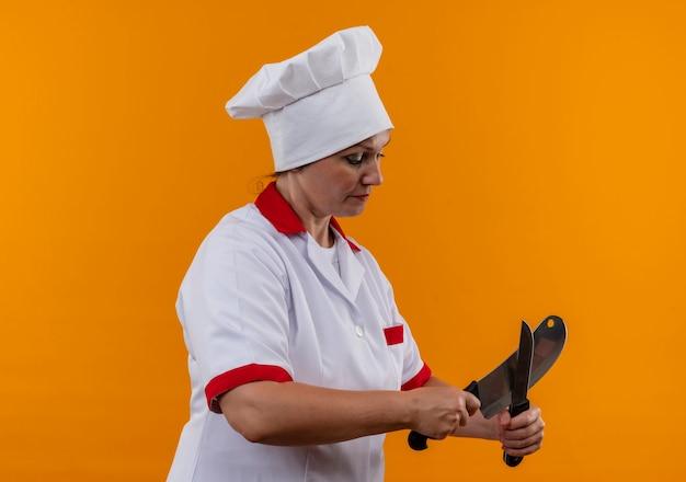 Staande in profiel bekijken vrouwelijke kok van middelbare leeftijd in chef-kok uniform sharpes mes Gratis Foto