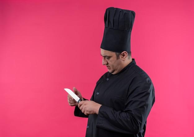 Staande in profiel te bekijken mannelijke kok van middelbare leeftijd in eenvormige chef-kok die mes in zijn hand met exemplaarruimte bekijkt Gratis Foto