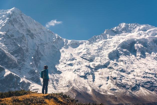 Staande jonge vrouw op de heuvel en kijkend op verbluffende himalaya-bergen Premium Foto