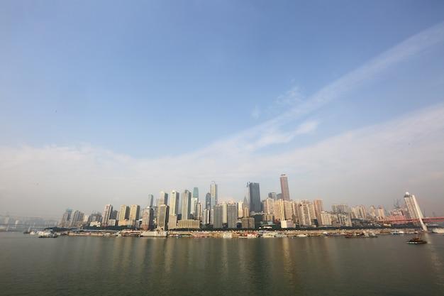 Stad scape van sky scrapper op rivieroever en weerspiegelt water en luchtwolk in dagtijd Premium Foto