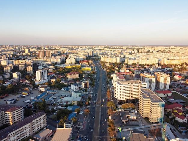 Stadsgezicht van boekarest, weg met bewegende auto's, meerdere woongebouwen, heldere hemel, uitzicht vanaf de drone, roemenië Gratis Foto