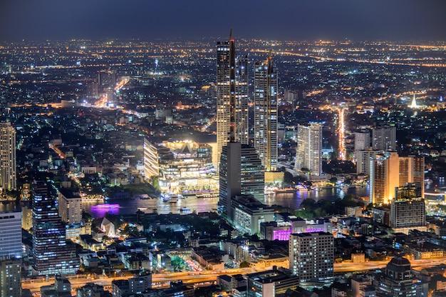 Stadsgezicht van verlichte gebouw met warenhuis in de buurt van de chao phraya-rivier Premium Foto