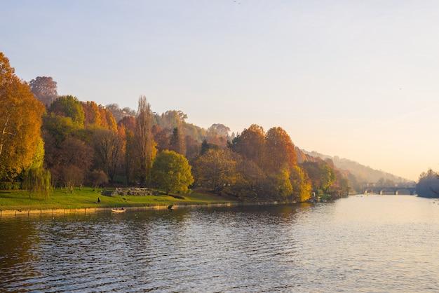 Stadsmening van turijn (turijn - italië) bij zonsondergang in de herfstseizoen met kerk op heuveltop die po-rivier en kleurrijke bomen overzien. Premium Foto