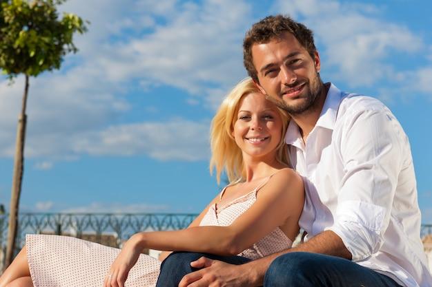 Stadstoerisme - paar in vakantie op een bank Premium Foto