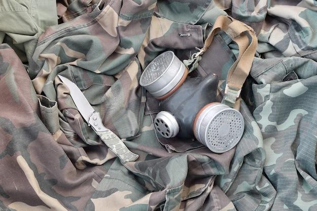 Stalker soldaten sovjet gasmasker ligt met mes op groene kaki camouflage jassen. post-apocalyps overlevende items kit Premium Foto