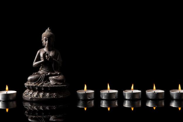 Standbeeld van boeddha zittend in meditatie, kaars lijn met zwarte kopie ruimte Premium Foto