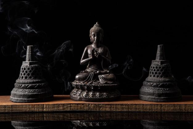 Standbeeld van boeddha zittend in meditatie, met boeddhistische klokken en wierookrook Premium Foto