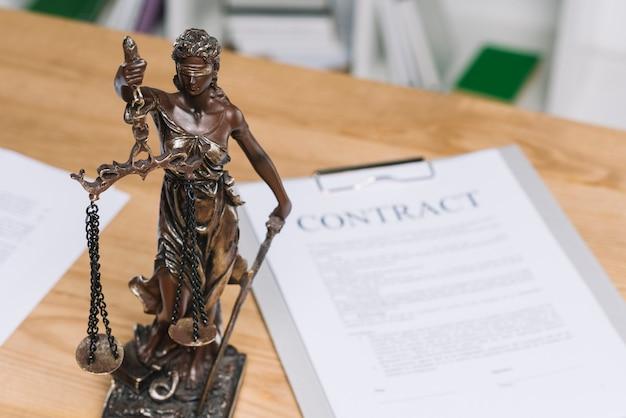 Standbeeld van rechtvaardigheid boven de tafel met contract papier Premium Foto