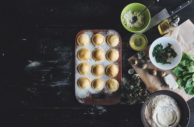 Stap voor stap bereidt de chef-kok ravioli met ricottakaas, dooierkwartelseieren en spinazie met kruiden. de chef-kok bereidt zich voor op het bereiden van ravioli Premium Foto