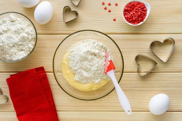 Stap voor stap recept voor het maken van koekjes voor valentijnsdag. meng met bloem, boter, suiker en ei in een glazen kom. Premium Foto