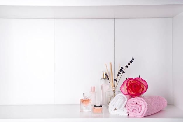 Stapel badhanddoeken met roos en parfums op lichte achtergrond Premium Foto