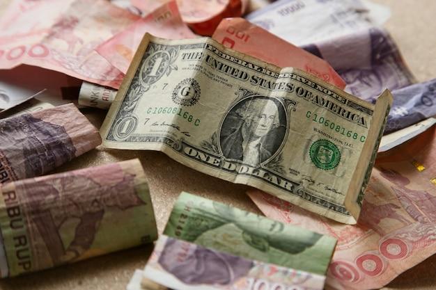 Stapel bankbiljetten uit verschillende landen op een houten ondergrond Gratis Foto