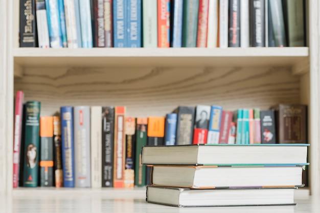 Stapel boeken dichtbij boekenkast in bibliotheek Foto | Gratis Download