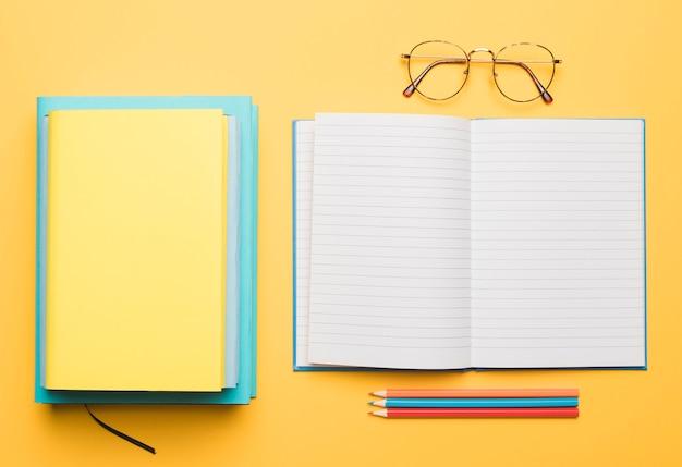 Stapel boeken en het openen van leeg voorbeeldenboek met geschikte potloden Gratis Foto