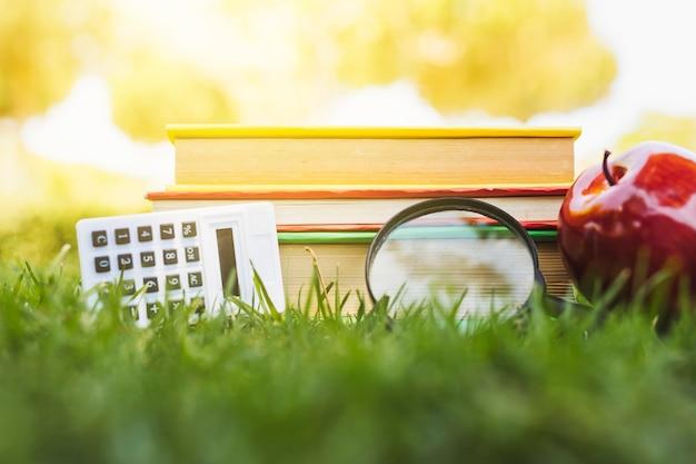 Stapel boeken met appel, rekenmachine en vergrootglas op gras Gratis Foto