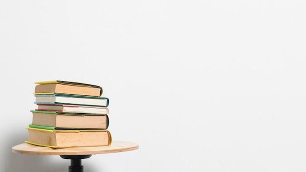 Stapel boeken op kruklijst aangaande grijze achtergrond Gratis Foto
