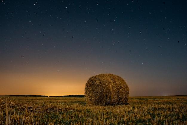 Stapel droog hooi onder de nachthemel met sterrenachtergrond Premium Foto
