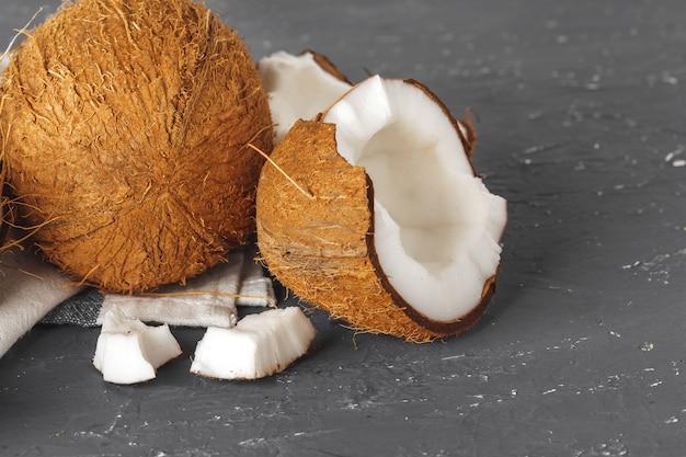 Stapel gebroken kokosnoten op gescheurde grijze achtergrond Premium Foto