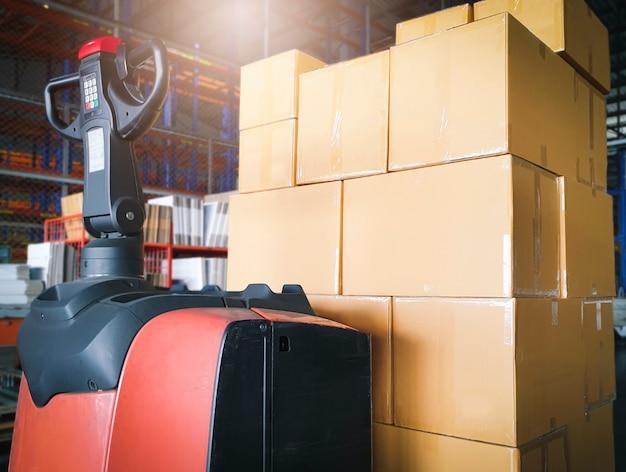 Stapel kartonnen dozen en heftruck palletkrik in het magazijn. vracht verzending en opslag. Premium Foto