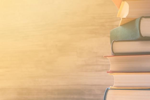 Stapel kleurrijke pastelkleurboeken op een plank in de bibliotheek. zonnestralen vallen op de boeken door het raam. onderwijs concept. terug naar school achtergrond. Premium Foto