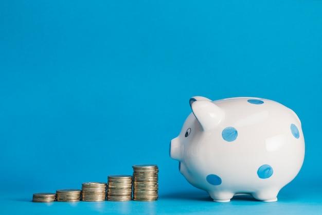 Stapel oplopende munten met keramische spaarpot tegen witte achtergrond Gratis Foto