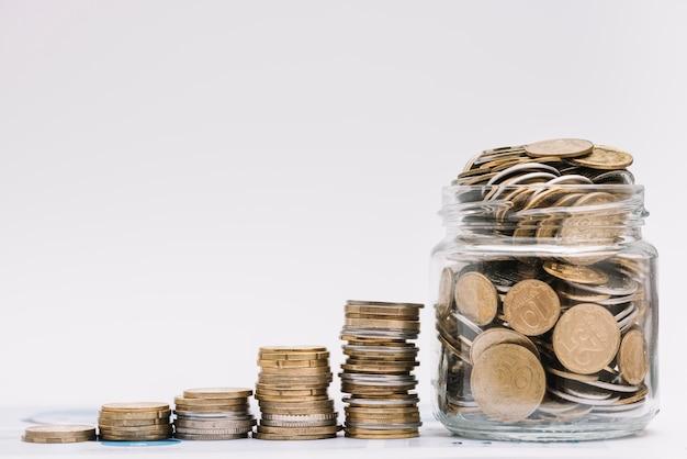 Stapel oplopende munten met pot gevuld met munten tegen witte achtergrond Premium Foto