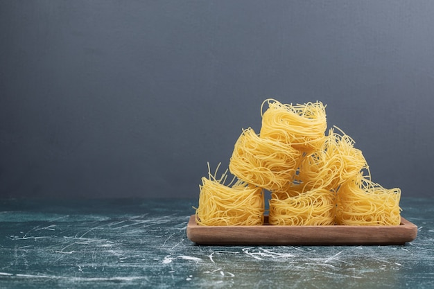 Stapel rauwe spaghetti nesten op een houten bord. hoge kwaliteit foto Gratis Foto