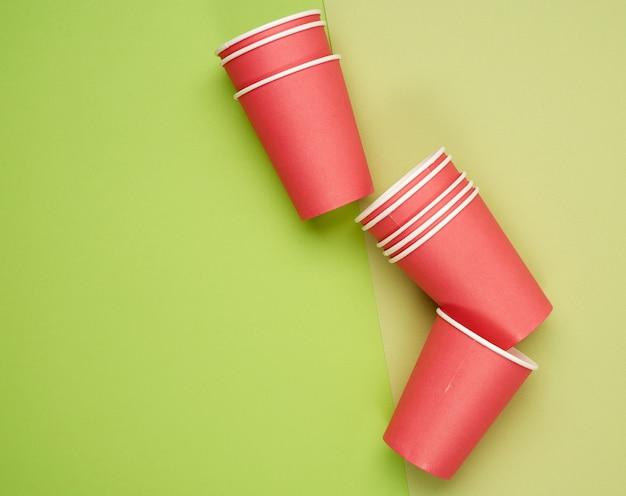 Stapel rode papieren wegwerpbekers op een blauwe achtergrond, plat leggen, concept milieuvriendelijk, nul afval Premium Foto