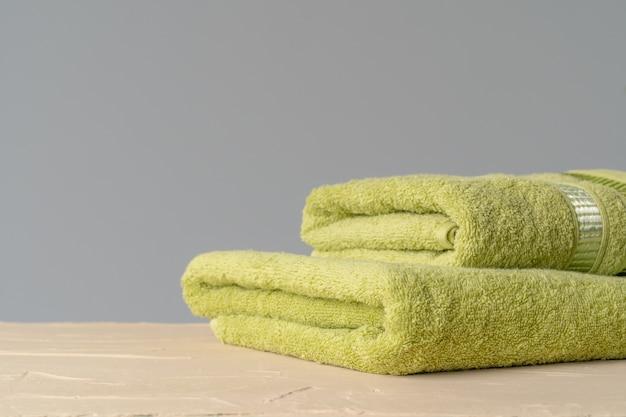Stapel schone nieuwe handdoeken tegen grijze muur Premium Foto