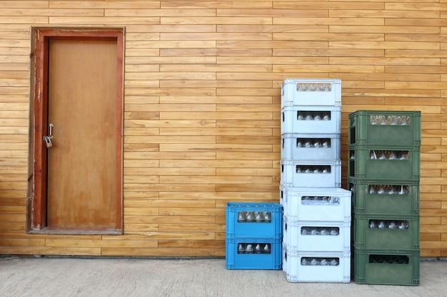 Stapel soda plastic blauwe, groene kleur krat aan de achterkant van bar pub met grote mooie houten muur en deuren op betonnen vloer Premium Foto