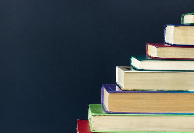 Stapel stappen trappen van oude boeken op zwarte schoolbord achtergrond Premium Foto