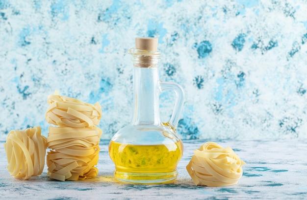 Stapel tagliatelle nesten en een glas olijfolie op blauw. Gratis Foto