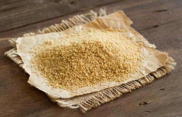 Stapel van gehele tarwe couscous op houten lijst dichte omhooggaand Premium Foto