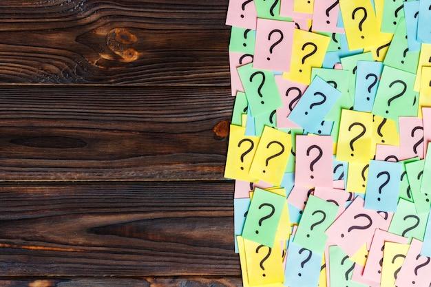 Stapel van kleurrijke papieren notities met vraagtekens. bovenaanzicht kopie ruimte Premium Foto