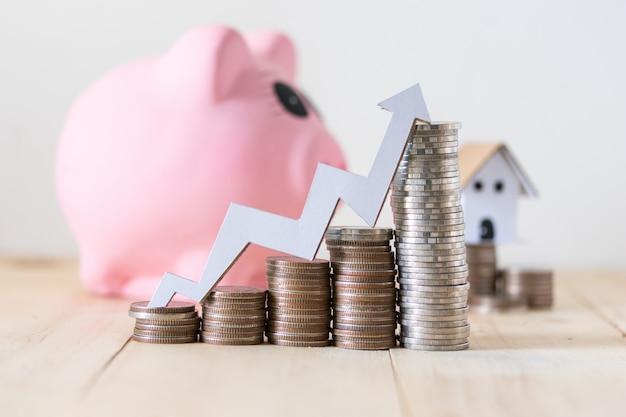 Stapel van munten en spaarvarken, sparen en investeringsconcept met stijgende grafiek op bovenkant Premium Foto