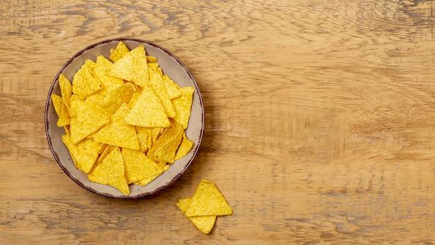 Stapel van nachos op plaat op houten tafel Gratis Foto