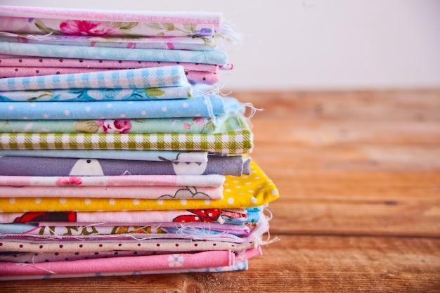 Stapel van nieuwe stoffen in verschillende kleurendoek op de houten lijst Premium Foto