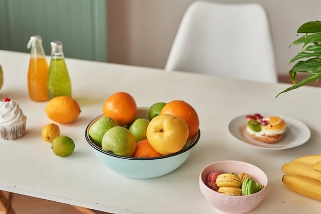 Stapel van rijp fruit op tafel met zoete macarons en sappen Premium Foto