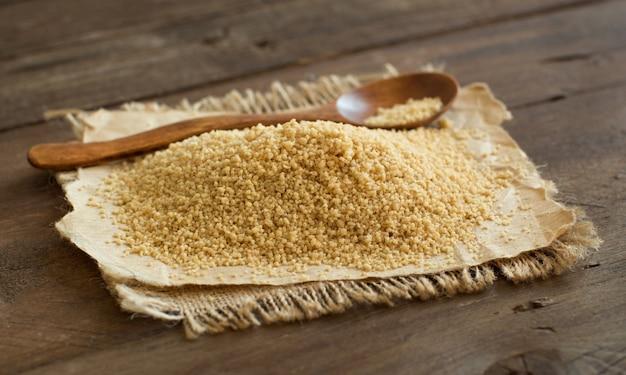Stapel van volkoren couscous met een lepel op een houten tafel close-up Premium Foto