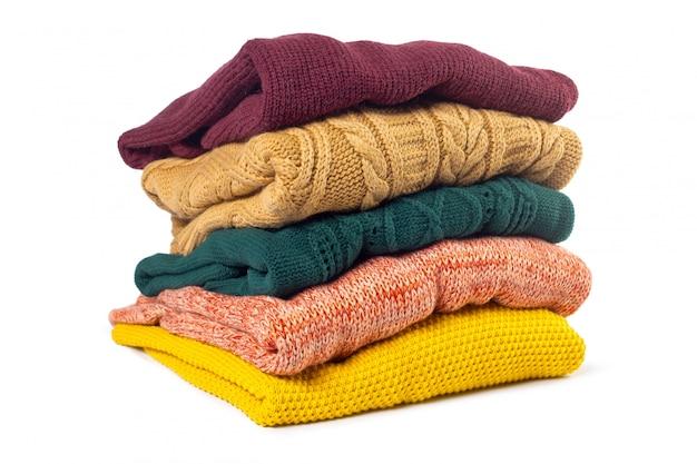 Stapel verschillende sweaters geïsoleerd op wit Premium Foto