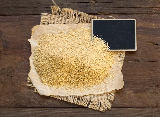 Stapel volkoren couscous met een klein bord bovenaanzicht op hout Premium Foto