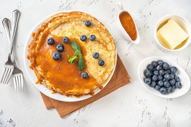 Stapel zelfgemaakte pannenkoeken gegarneerd met karamel en verse bosbessen Premium Foto