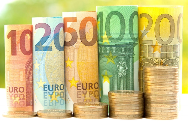 Stapels munten en opgerolde eurobankbiljetten Premium Foto