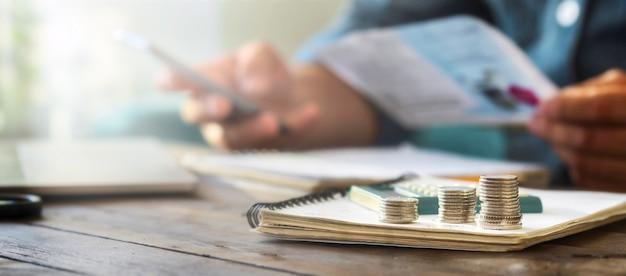 Stapels munten op een houten tafel met rekenmachine op de achtergrond controleert een man huishoudelijke rekeningen Premium Foto